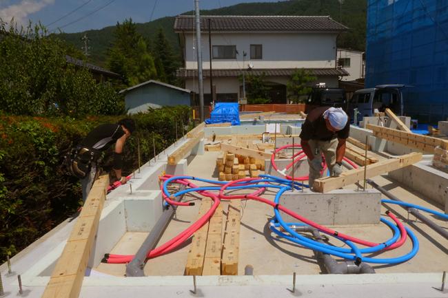 大工さんが基礎に土台を据え付けている写真